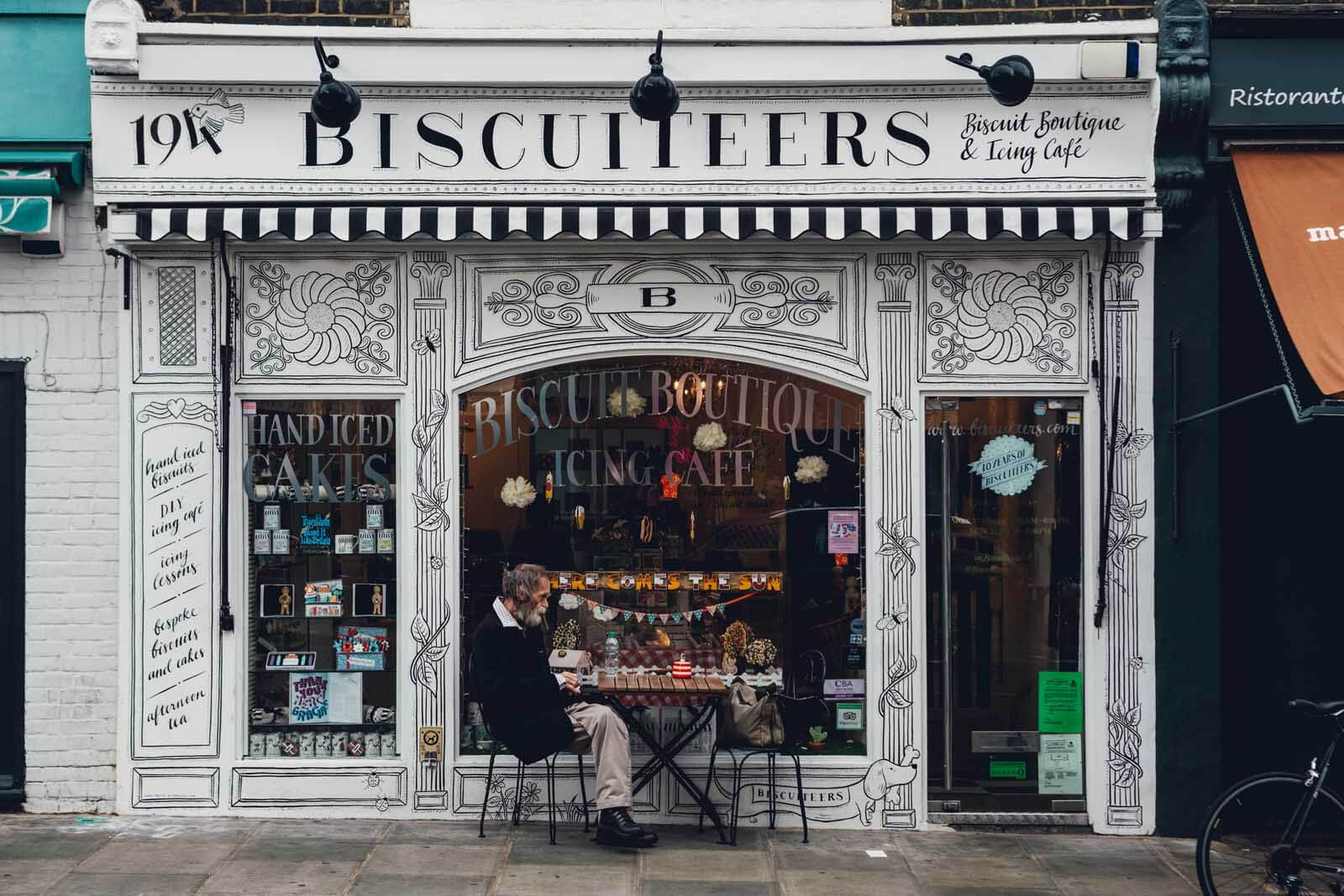man sitting at Biscuiteers Bakery and Icing Shop in London