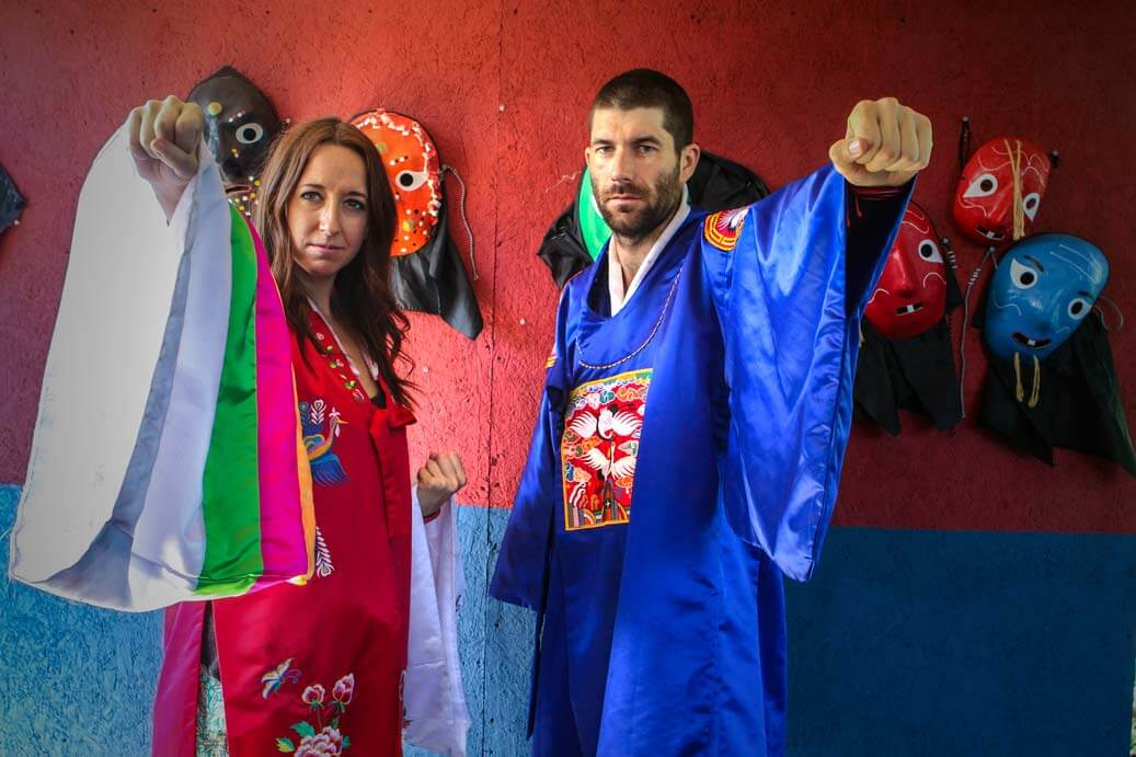 An american couple wearking Korean hanbok and holding their fists out