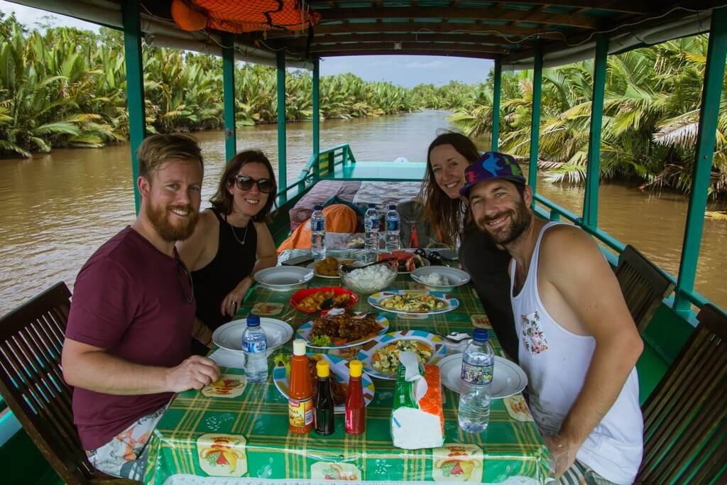 The four of us enjoying lunch on the klotok during our river cruise through the jungle of Borneo Indoneisa