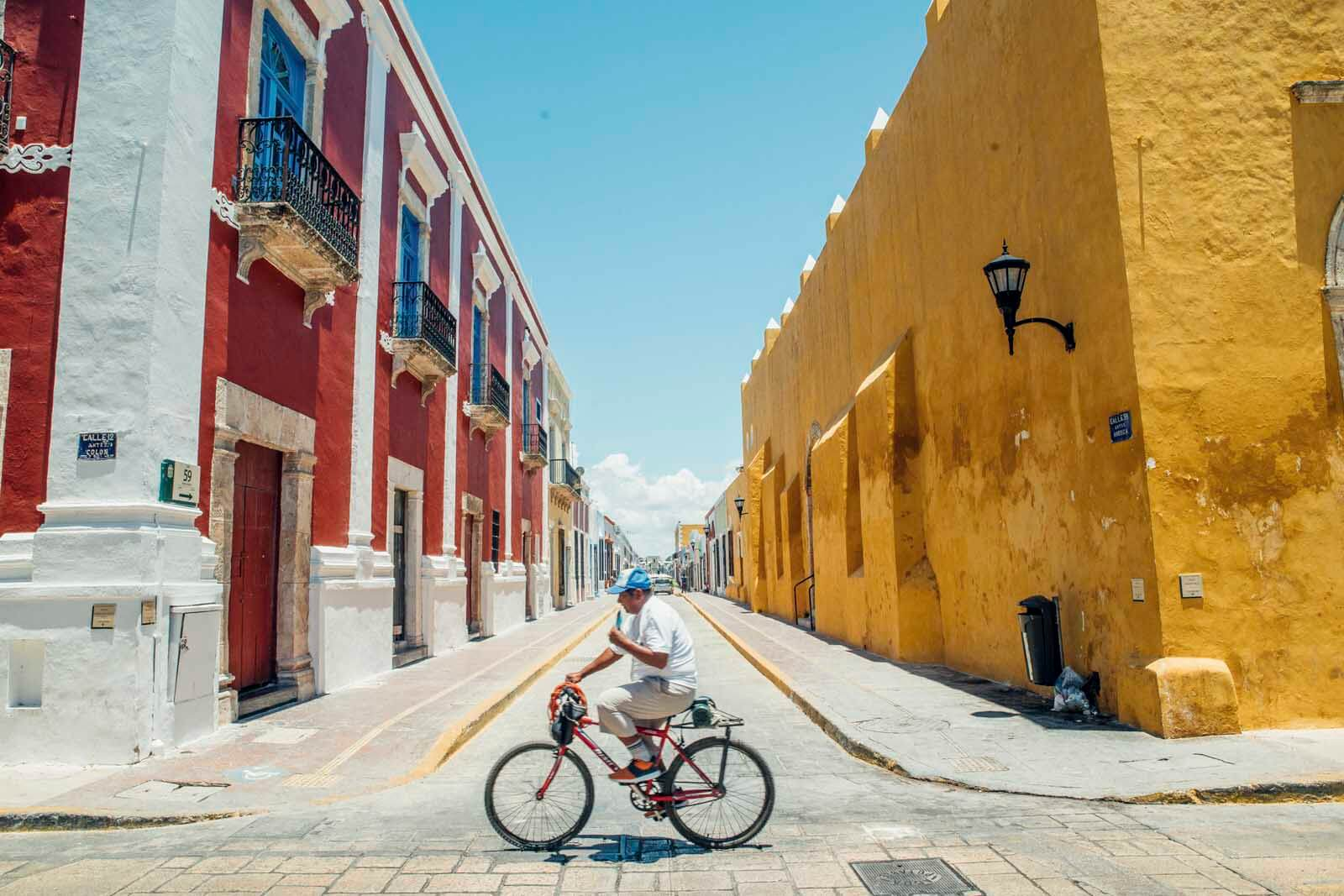 Man cycling down the streets of Campeche Mexico