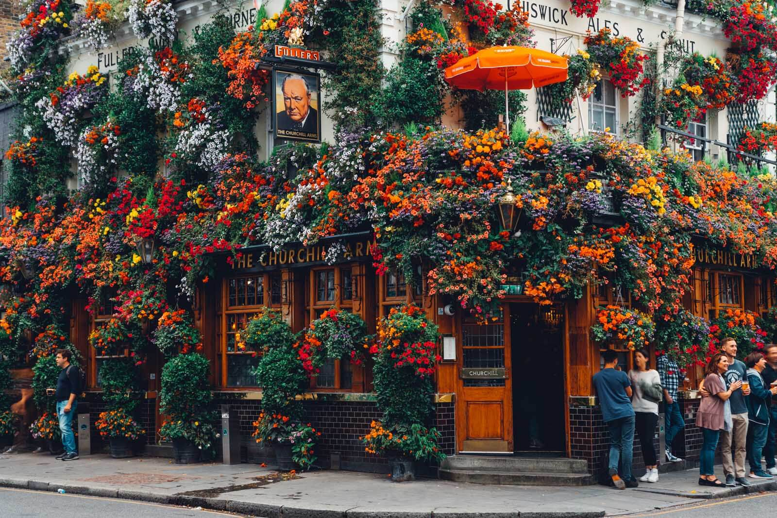 people gathering around the flowery Churchill Arms Bar in London