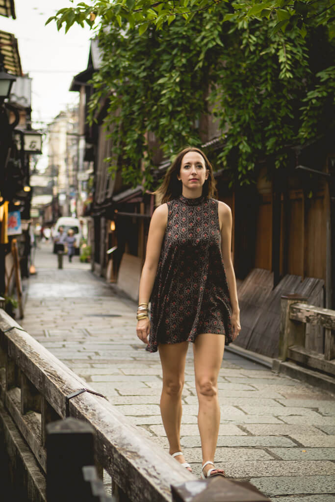 Girl in short patterned dress walking on streets of Gion