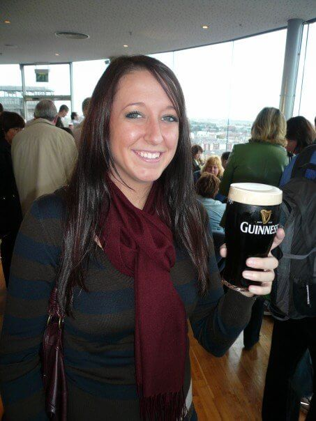 A brunette girl holding a pint of guinness at the guinness factory in dublin