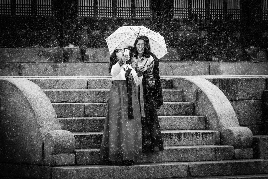 Girls Laughing Taking Selfies in the snow at Gyeongbokgung Palace in black and white
