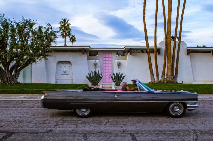 Man driving a classic car past the pink door house in Palm Springs California