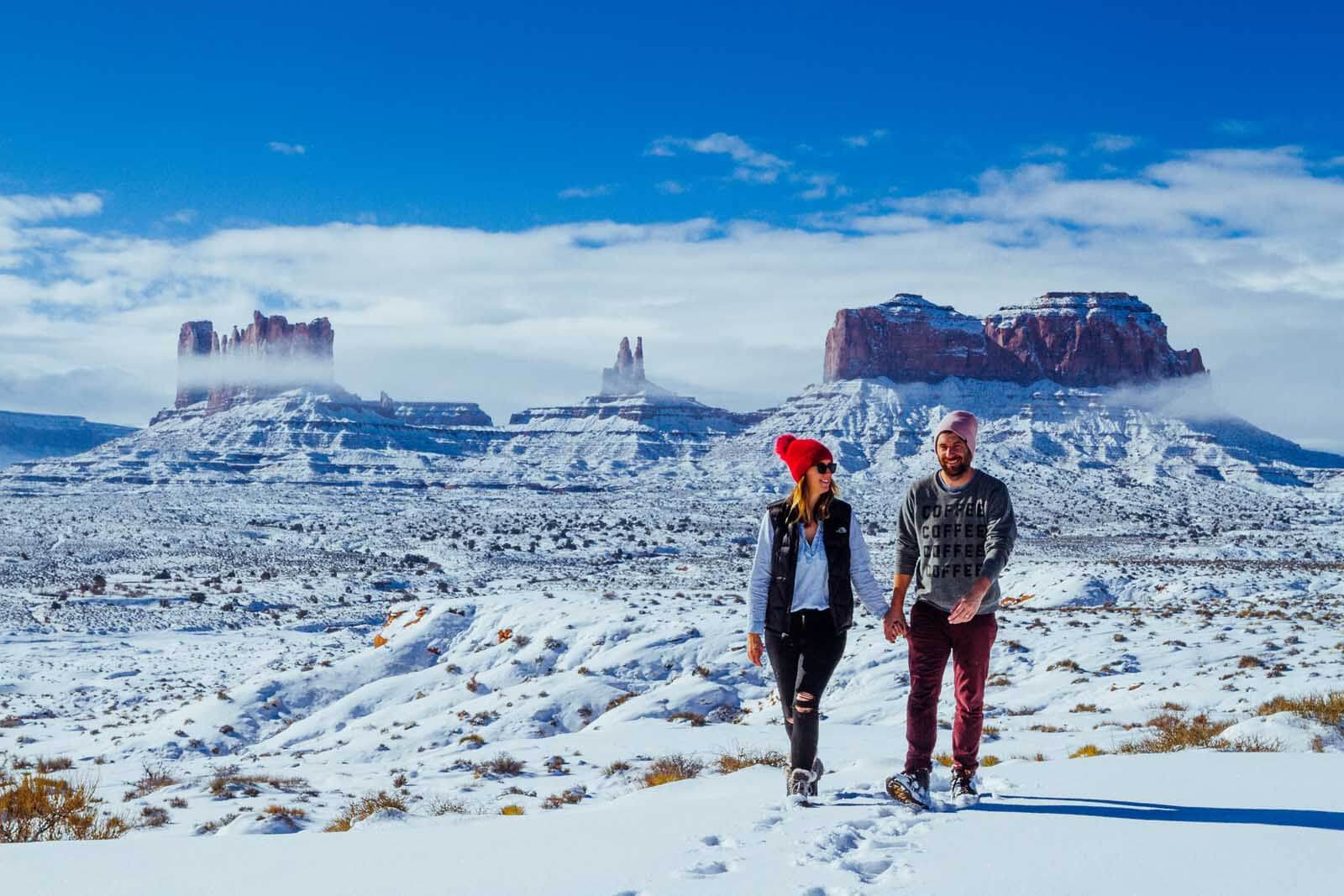 Megan and Scott walking in snow with Monument Valley in the background