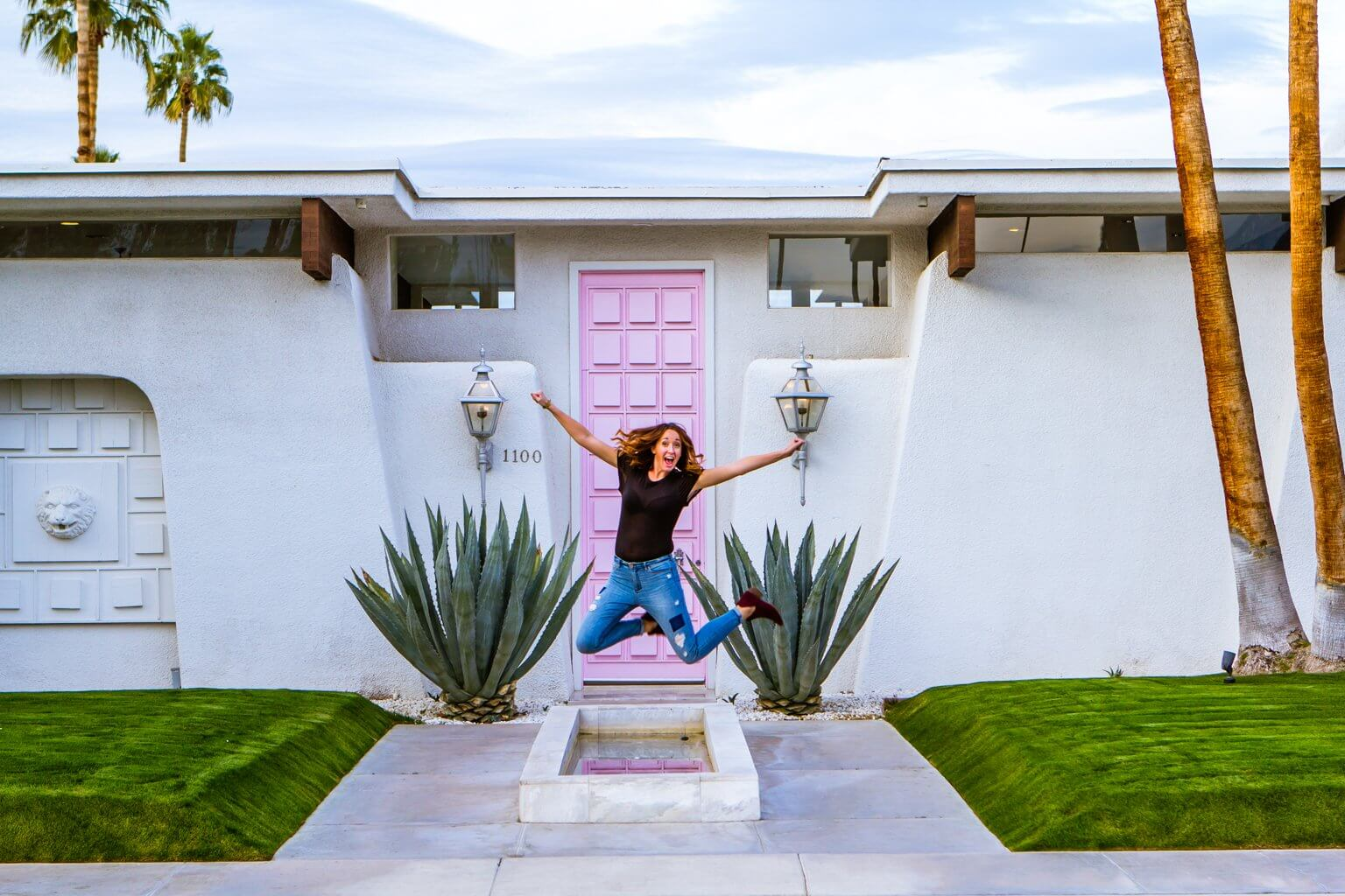 Megan jumping in front of that pink door famous house in palm springs