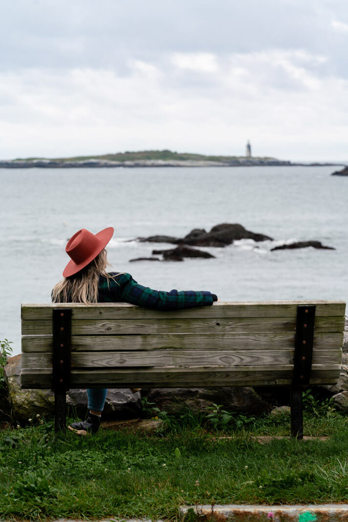 Megan enjoying the view of a lighthouse in the distance from a bench on Peaks Island in Portland Maine