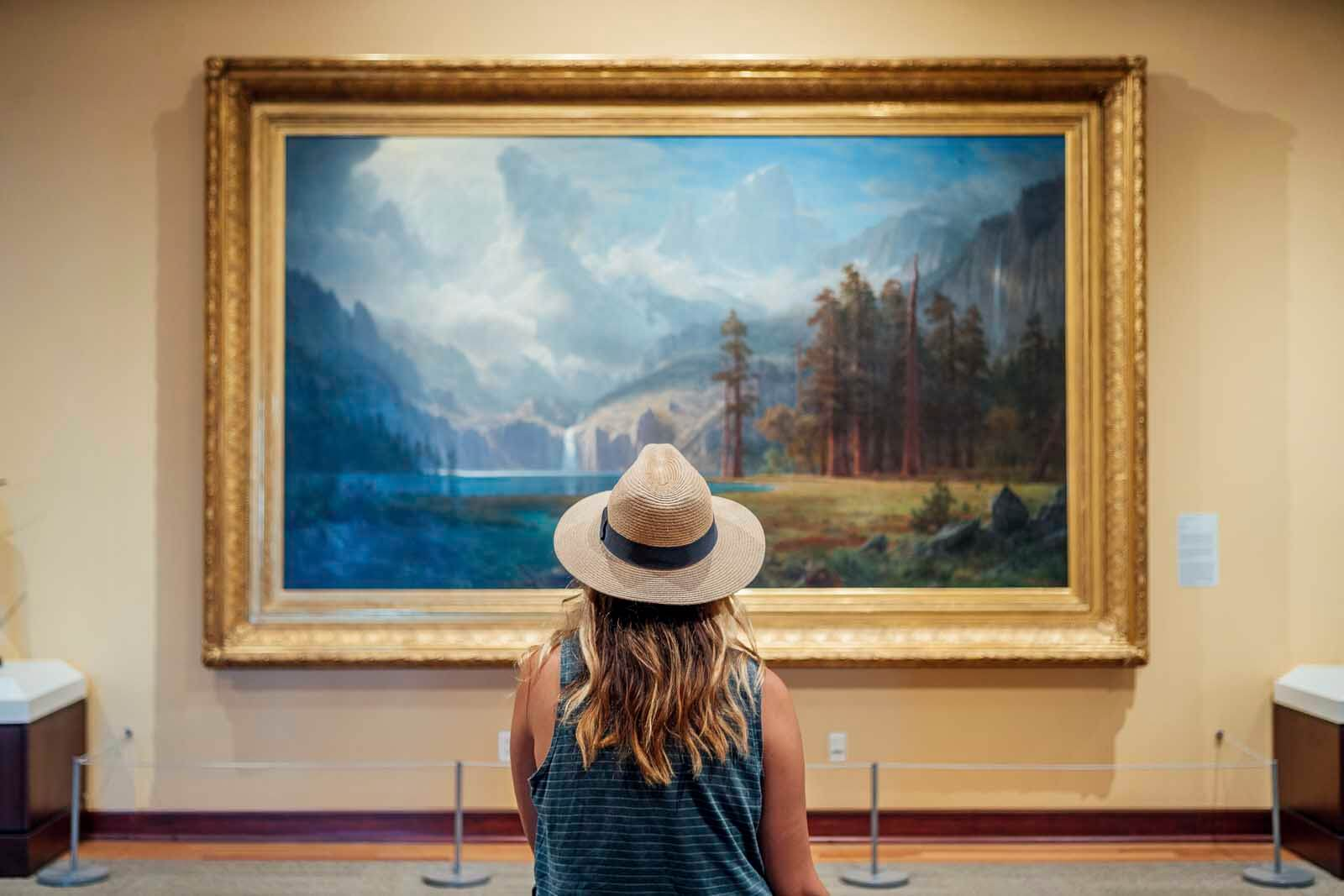 Megan sitting and looking at a landscape painting in Rockwell Museum in Corning