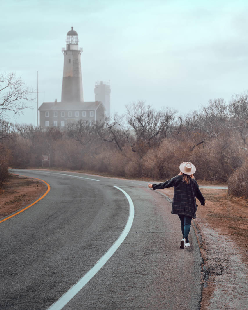 Megan pretending to hitchhike in the hamptons new york at Montauk Point Lighthouse