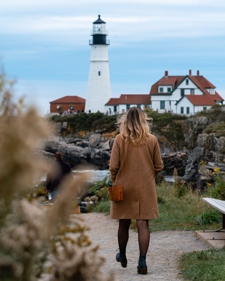 Megan walking on the lighthouse trail to Portland Head Light in Portland Maine