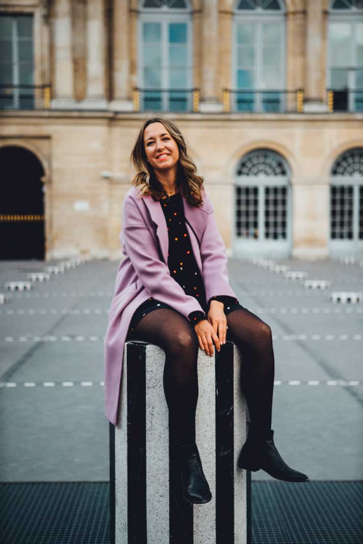 Megan sitting on the black and white columns at Palais Royal near the Louvre in Paris