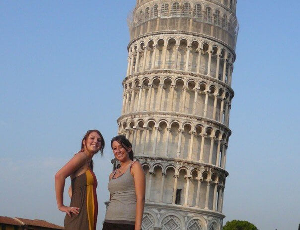 Two girls on European vacation standing in front of leaning tower of pisa in rome Italy