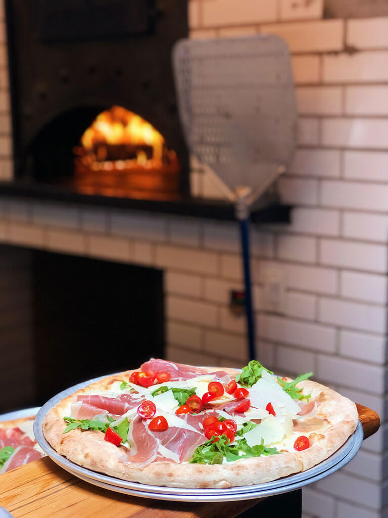 a pizza fresh from the wood fire oven at Emporio Nolita Restaurant