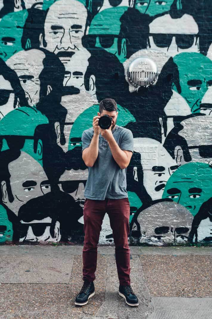 Scott taking a photo in front of a mural wall in East London