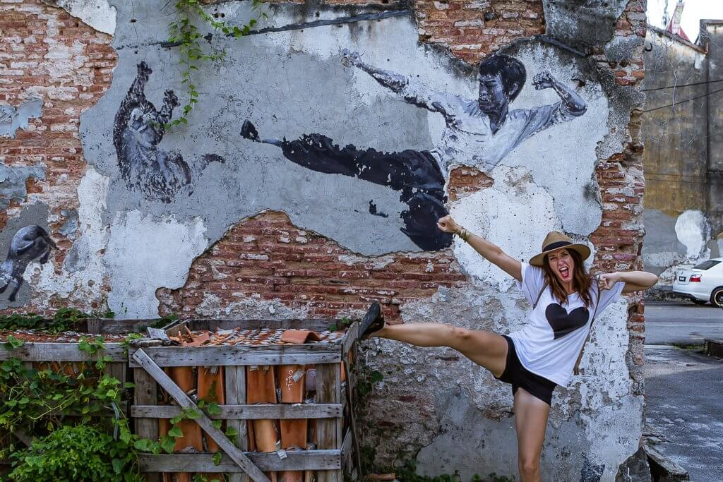 girl in hat and white t-shirt with black heart and black shorts pretending to kick at crate -- mimicking street art behind her of bruce lee in famous fighting pose on a gray and brick wall