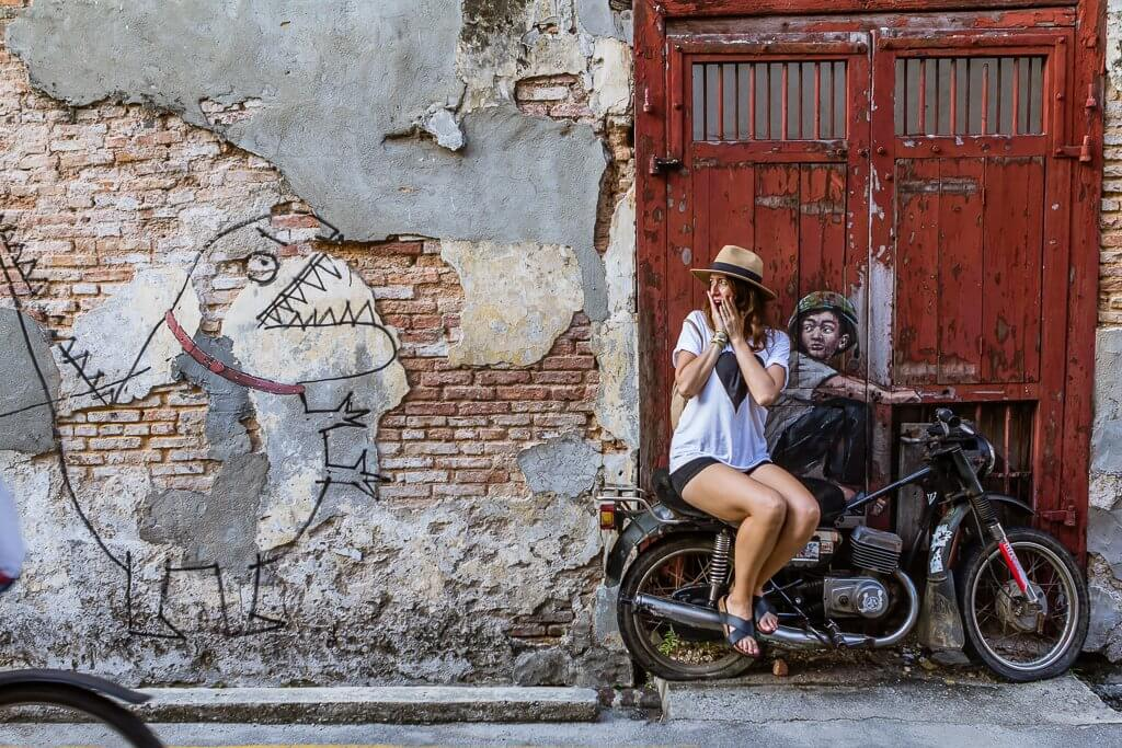 girl in straw hat, white t-shirt, and black shorts at street art scene in Penang -- street art is of a boy on a motorbike with a real motorbike in front on a red door to the right and a funny dinosaur outline to the left on a patchy brick wall.
