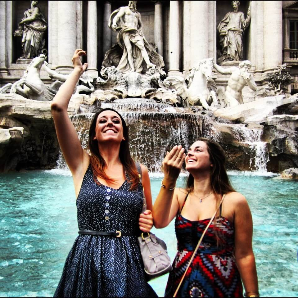 Two girls throwing coins over their back into the trevi fountain in Rome Italy