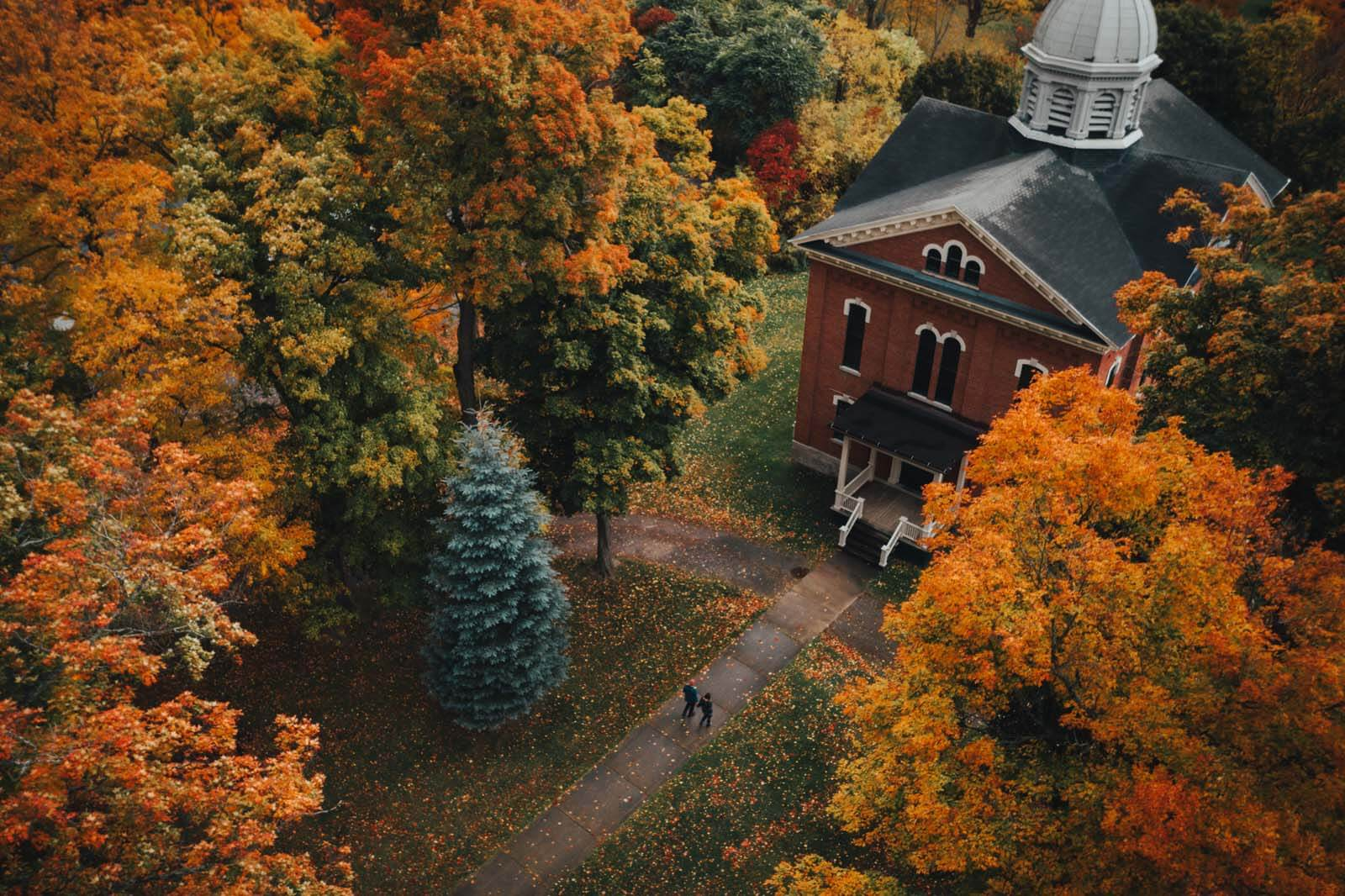 aerial shot of Megan and Scott walking to Naples Memorial Town Hall in New York Finger Lakes region in the fall