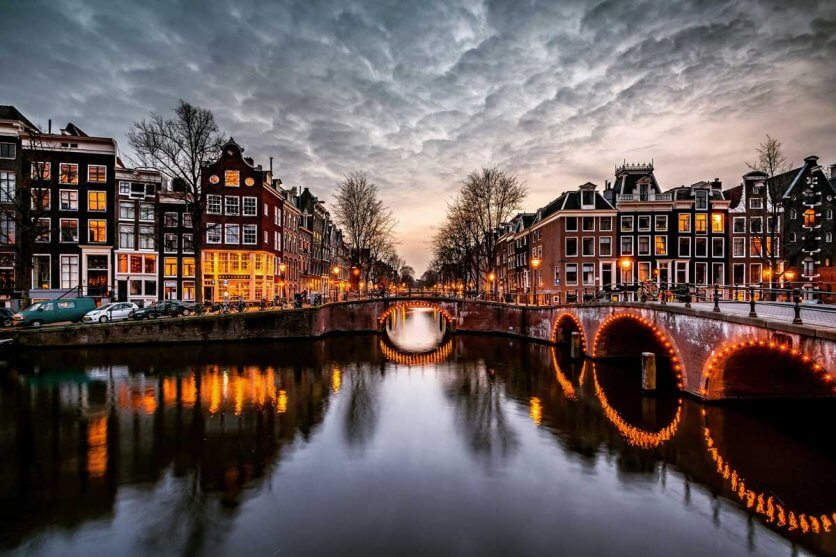 gorgeous-evening-shot-of-Amsterdam-and-dutch-style-homes-plus-the-canal-all-lit-up-at-night