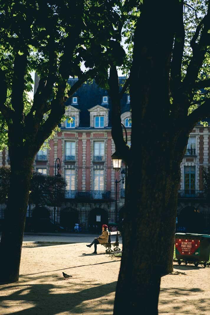lady on a bench at Place des Vosges in Le Marais PAris