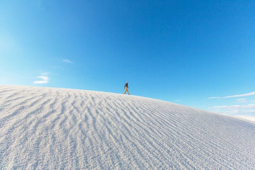 man-walking-on-the-white-sands-national-park-sand-dunes