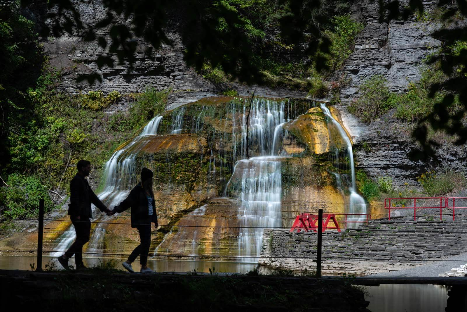 megan and scott walking in front of enfield falls at robert treman state park in ithaca ny