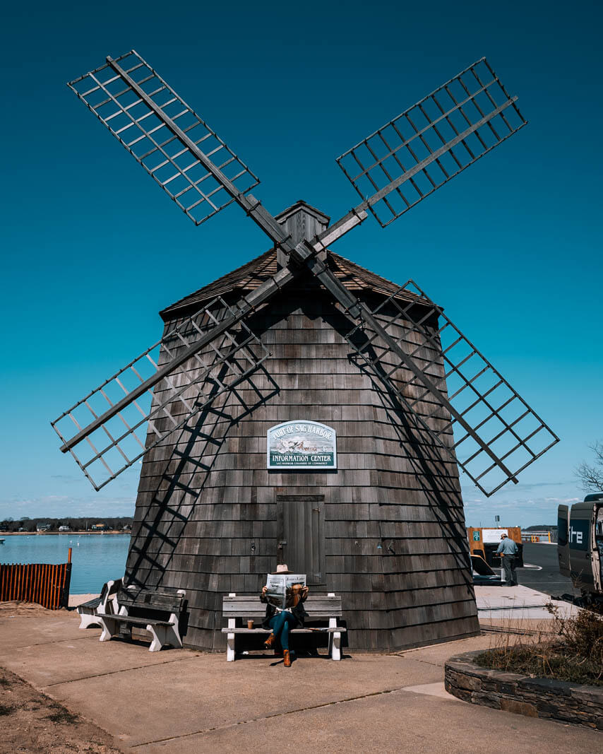 megan reading a newspaper under the windmill in Sag Harbor Hamptons New York