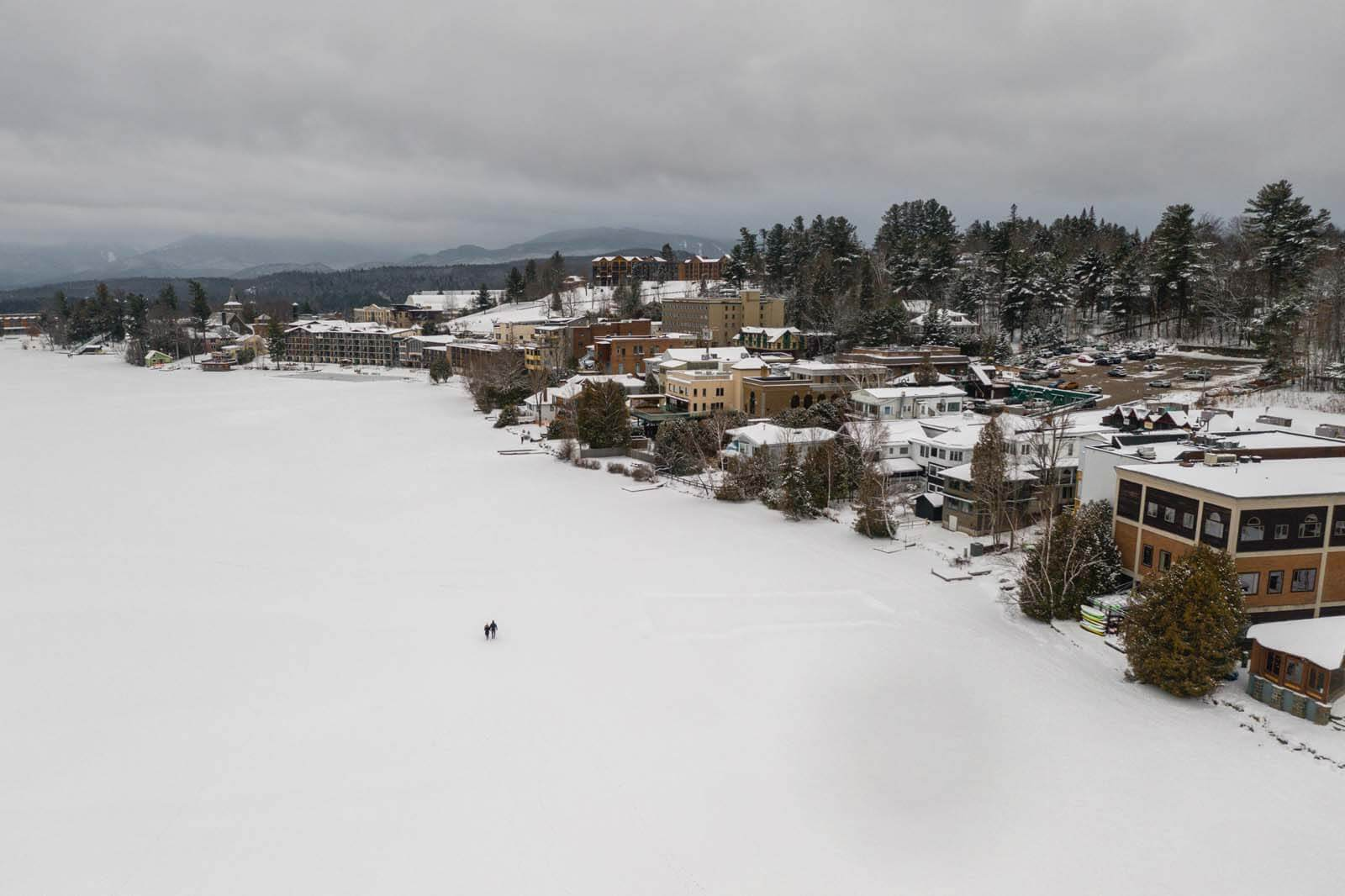people walking on the frozen mirror lake at Lake Placid in winter in the Adirondacks new york