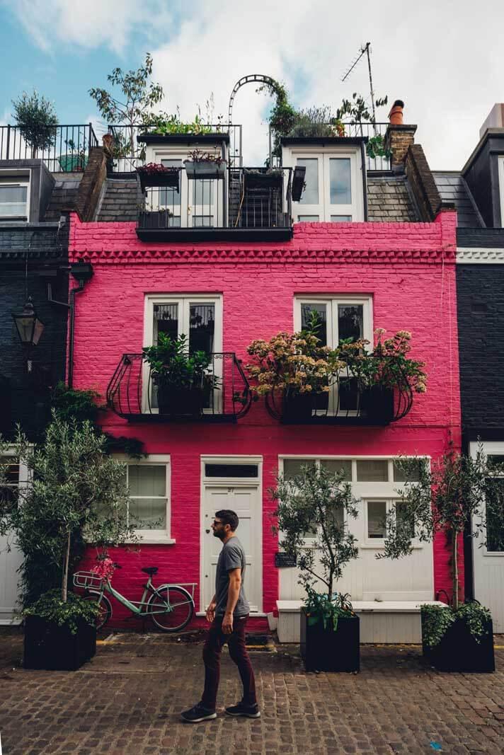 Scott walking across pink house in St Lukes Mews in Notting Hill London