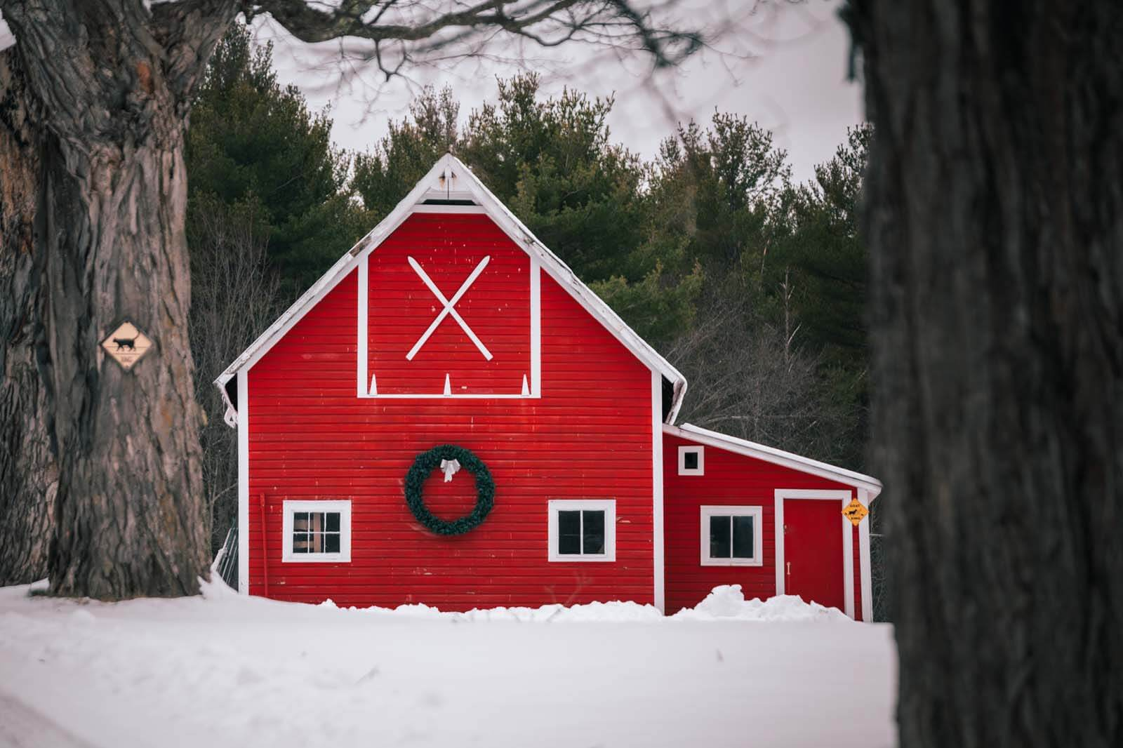 pretty red barn in the snow scene in Jay New York in the Adirondacks