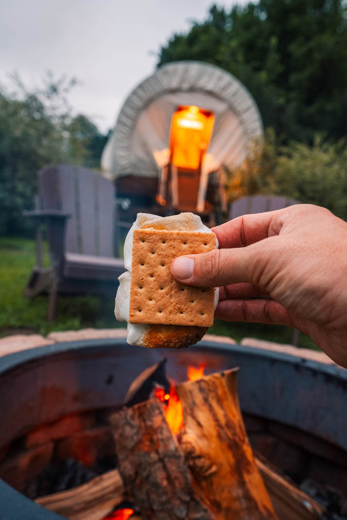 smores over a fire at the Conestoga Covered Wagons at Roscoe Campsite during a Catskills summer getaway in New York