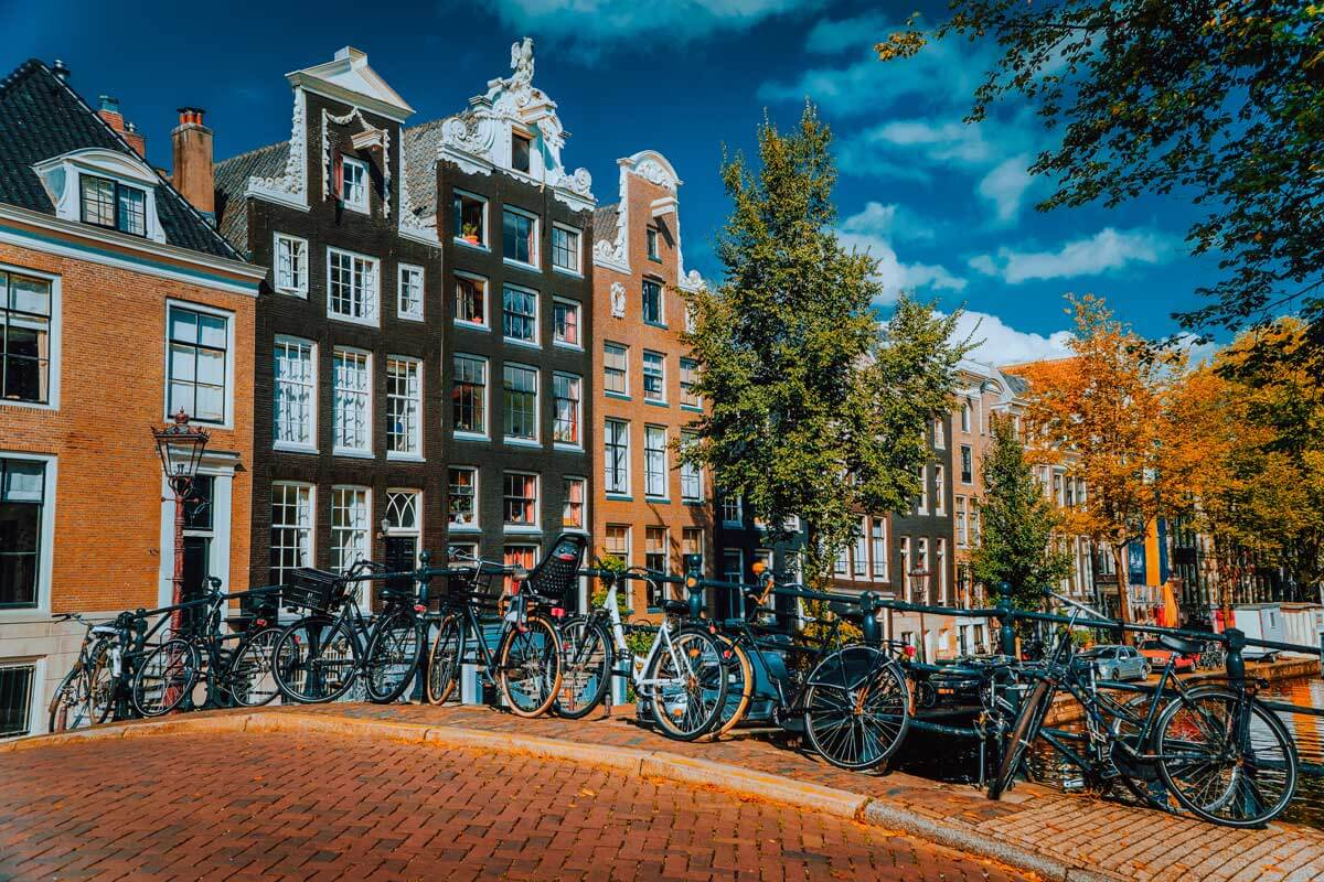 traditional-dutch-style-houses-in-amsterdam-netherlands-and-bicycles-lined-up-on-the-bridge-XC8KG3E