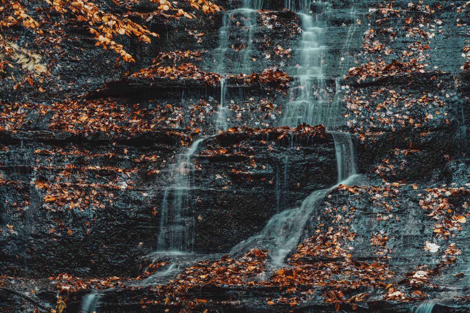 water cascading down the falls in Grimes Glen Park in Naples New York in the fall
